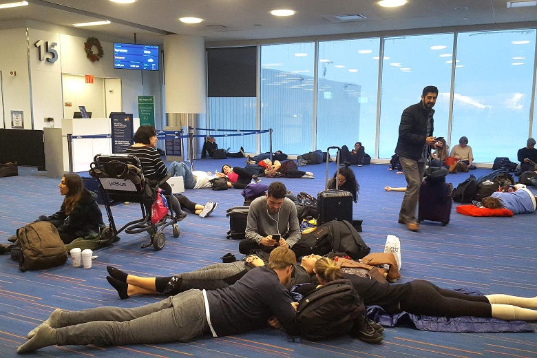 Passengers sit and lay on the floor of the airport.