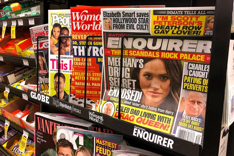 "A copy of the National Enquirer in a grocery store checkout lane. One headline about Prince Charles reads ""Paying off perverts."""