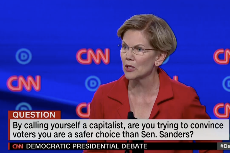 "In this screengrab from CNN, Elizabeth Warren debates. The banner reads: ""By calling yourself a capitalist, are you trying to convince voters you are a safer choice than Sen. Sanders?"""