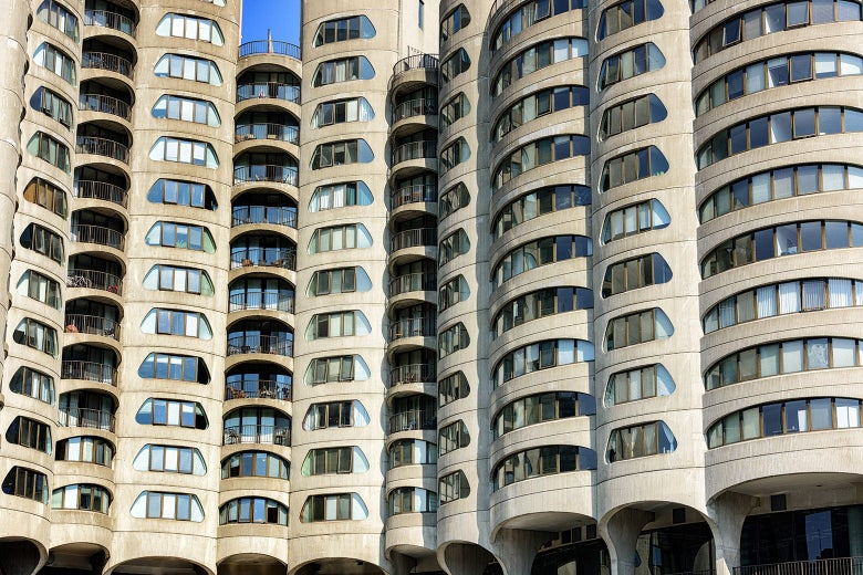 Tan-colored Brutalist apartment complex of cylindrical towers with window cutouts on each floor shaped like coin slots