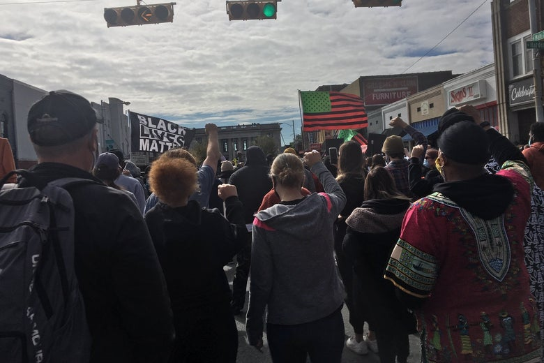 A crowd of people march down a street with a red, green, and black American flag and a Black Lives Matter flag