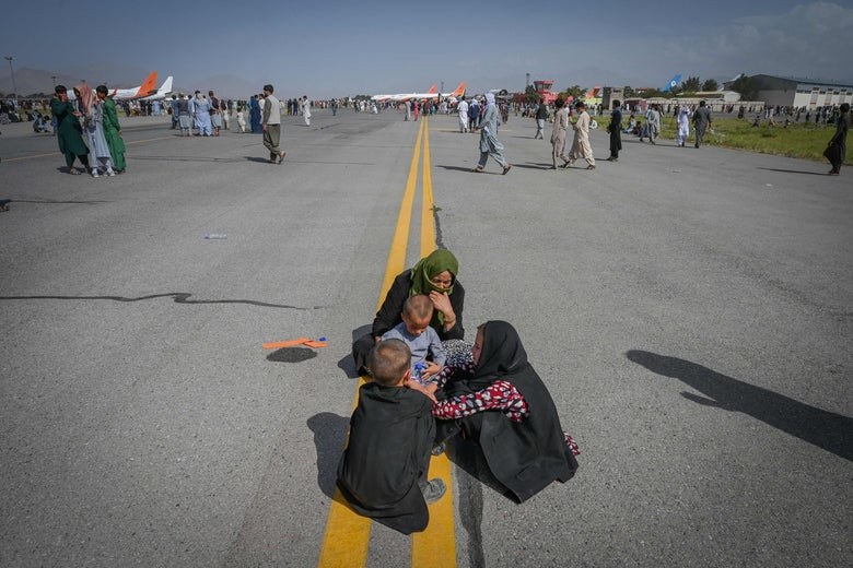 Afghans stand outside on the runway. In the foreground a family sits on the tarmac.