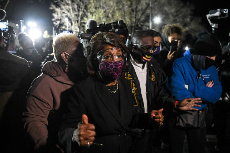 Maxine Waters stands outside in a crowd, wearing a mask and face shield.
