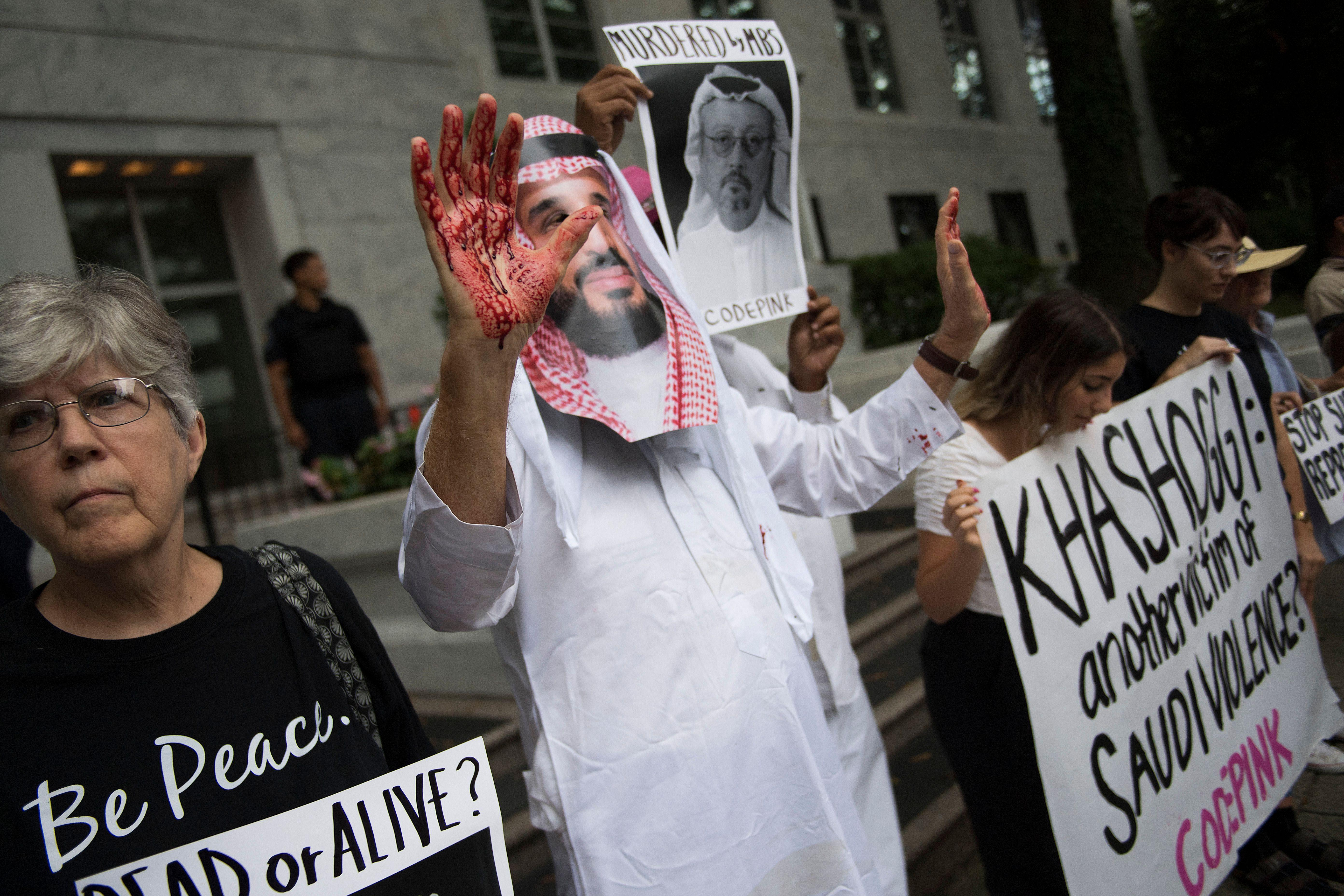 A demonstrator dressed as Saudi Arabian Crown Prince Mohammed bin Salman (C) with blood on his hands protests outside the Saudi Embassy in Washington, D.C. on October 8, 2018.