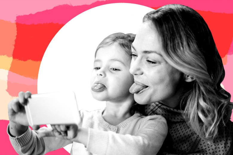 Mother and daughter taking a selfie together while sticking out their tongues