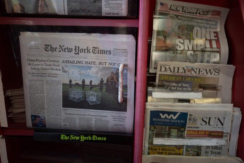Newspapers on racks.