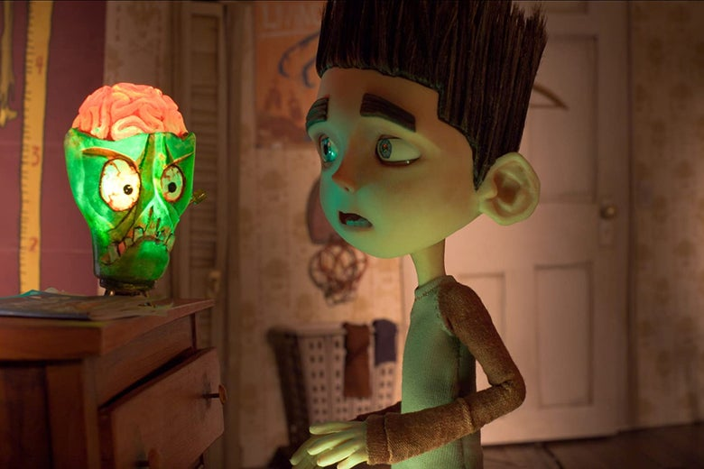 Norman Babcock looks at a glowing green skull lamp with an exposed brain.