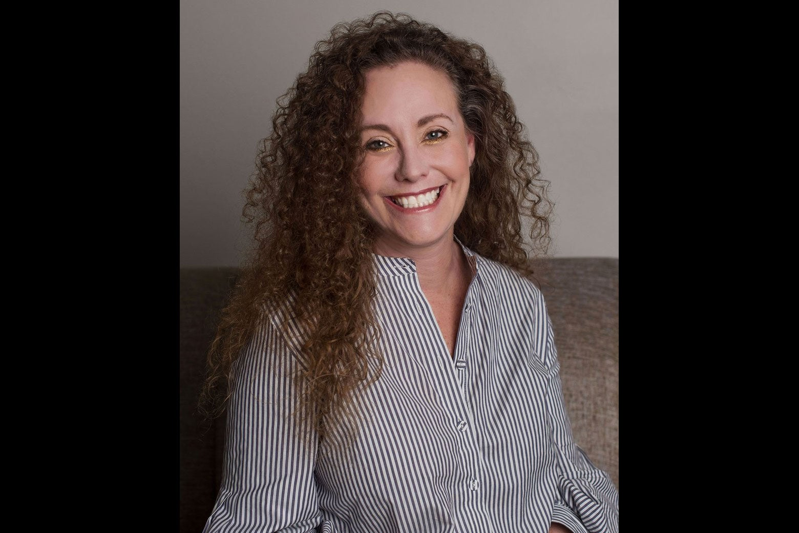 Swetnick, seated in a button-down shirt, smiles while looking into the camera.