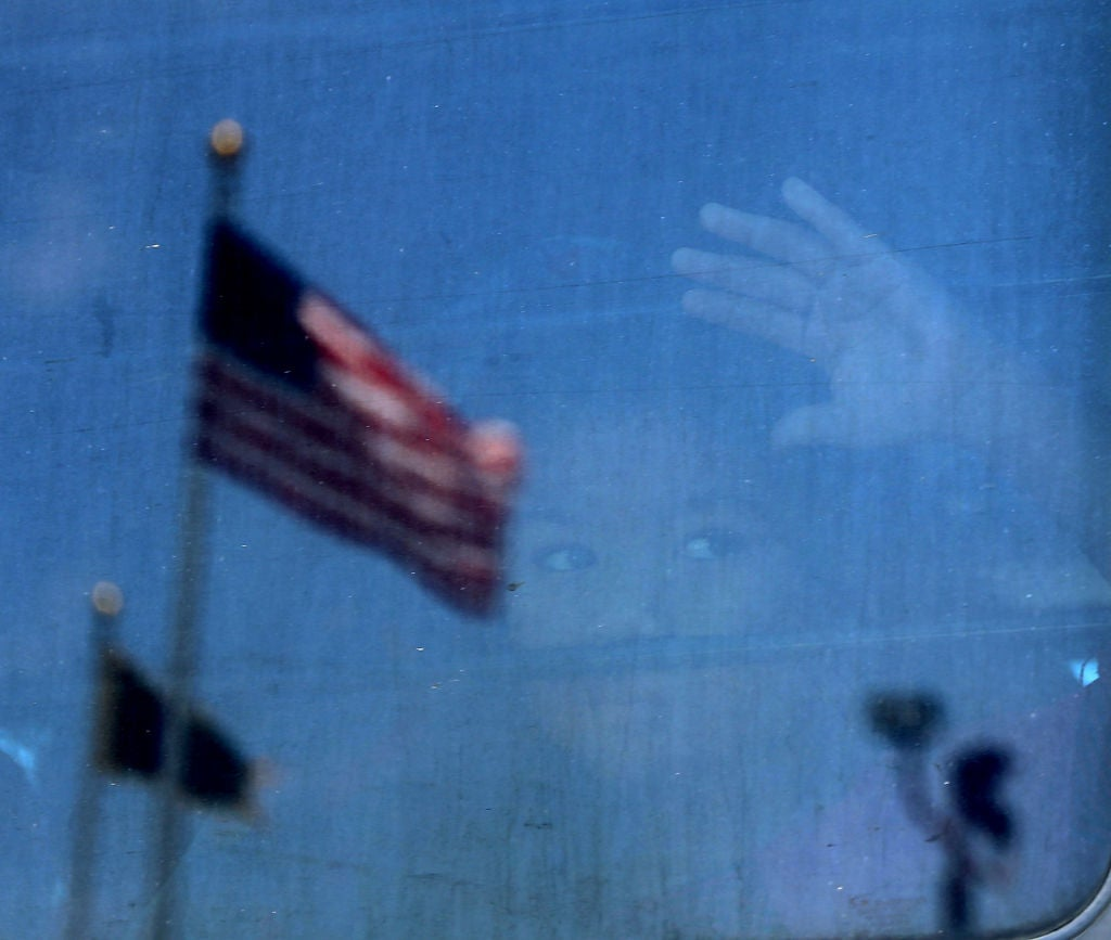 A young child's face can be seen through the window of a bus against which a United States flag is reflected.
