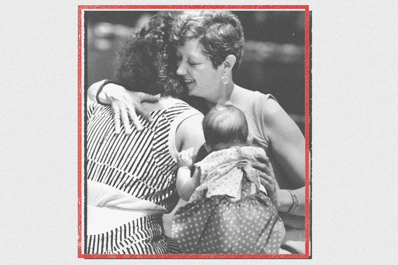 Photo of McCorvey smiling and embracing a woman and a baby in a red frame