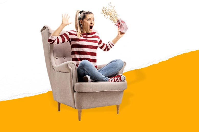 A woman sitting cross-legged on an easy chair throws her arms up, making the popcorn she was holding in her hand spill.