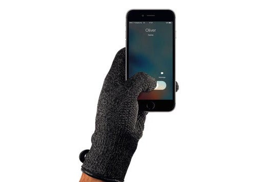 Hand wearing Mujjo glove while using a smartphone.