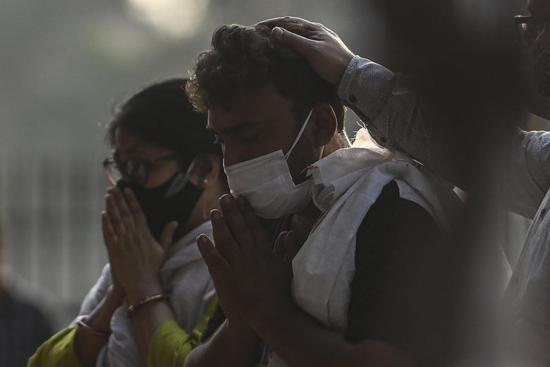 A man and a woman, both wearing masks, hold their hands in prayer to their mouths.