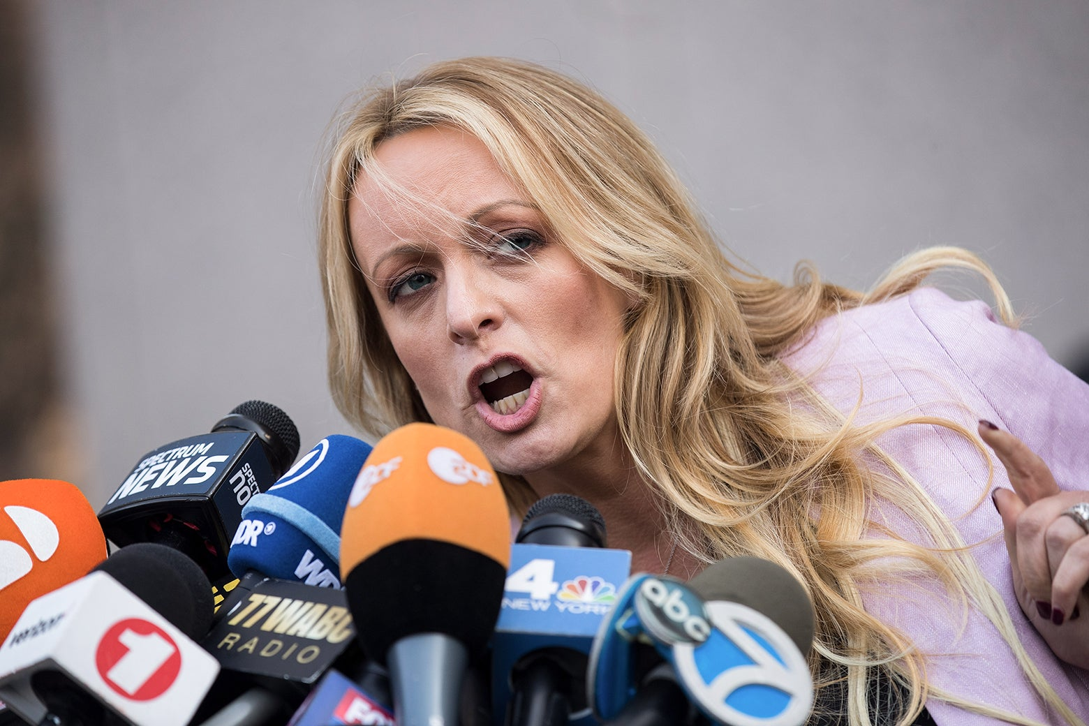 Stormy Daniels pointing and speaking into a scrum of microphones.