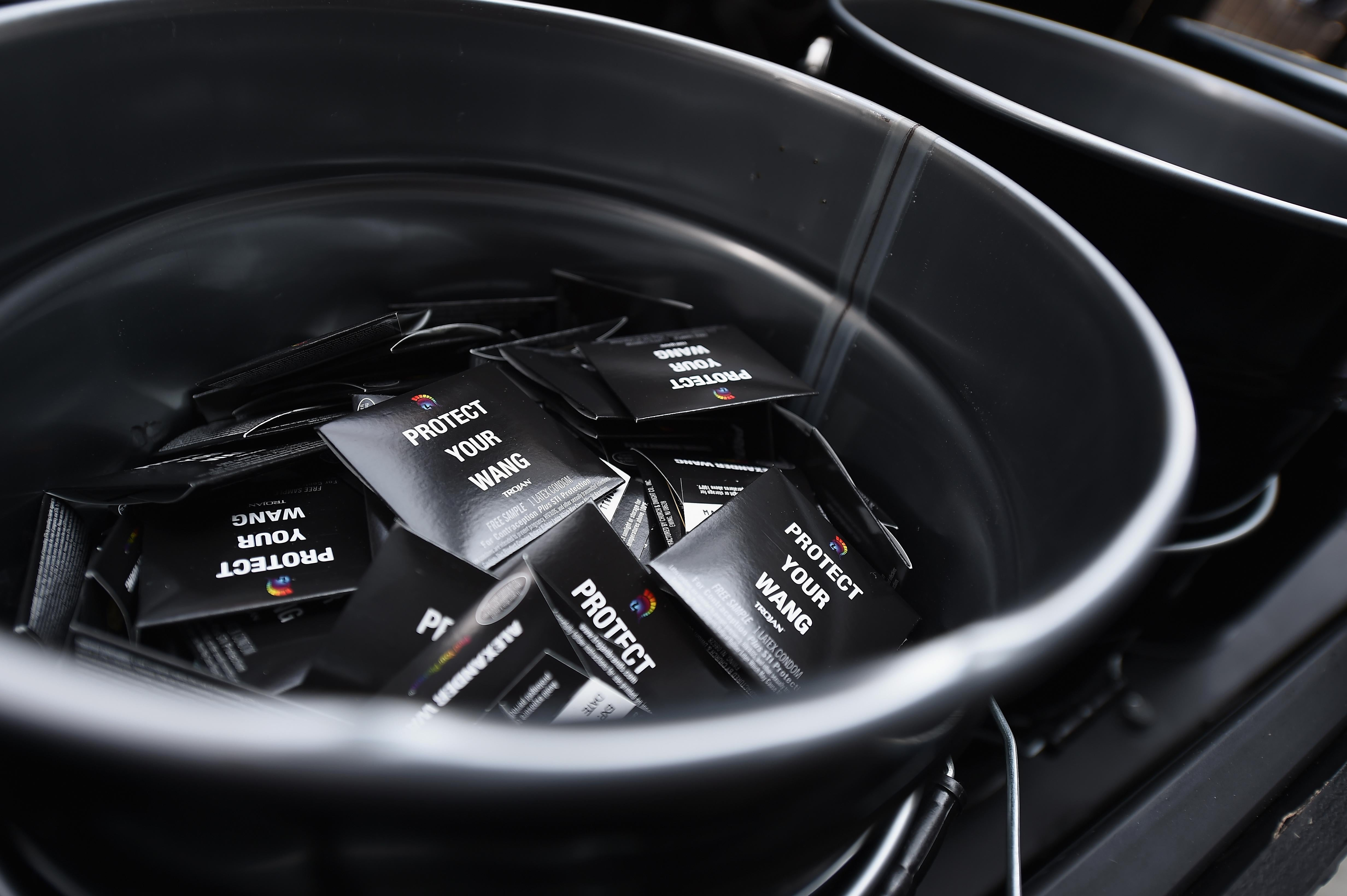 "Condoms in black packaging reading ""Protect Your Wang"" sit in a metal bucket."