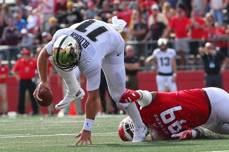 A Purdue quarterback stumbles as a Rutgers defensive lineman laying on the ground holds his left leg.