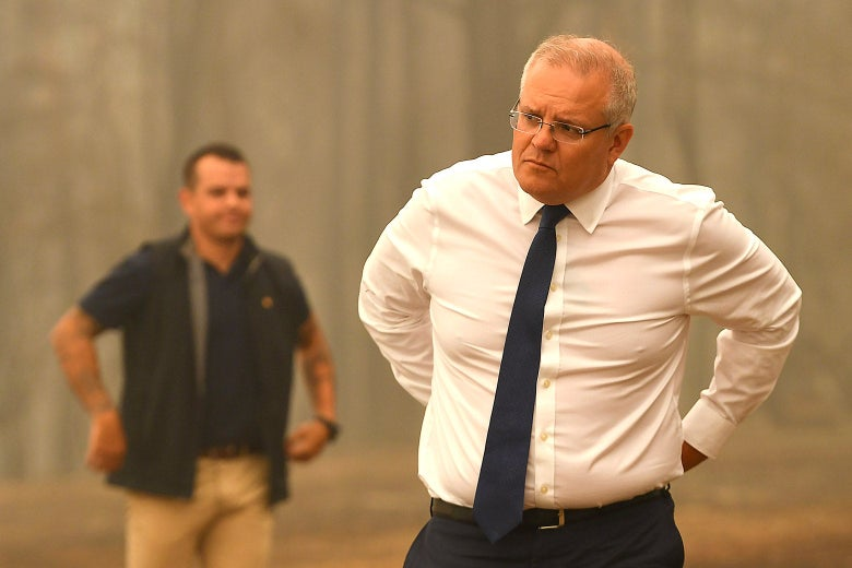 Scott Morrison, in shirt sleeves, with his hands behind his back.
