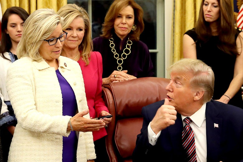 Liz Cheney, standing, speaks to Donald Trump, seated at the Resolute Desk. Several women stand behind them.