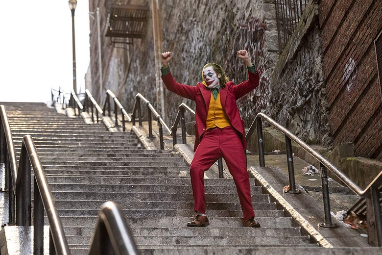 In a still from Joker, Joaquin Phoenix frolics in a maroon suit and clown makeup on an outdoor staircase.