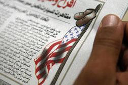 A man looks at an illustration in the December 16, 2008 edition of the Egyptian newspaper al-Badeel.