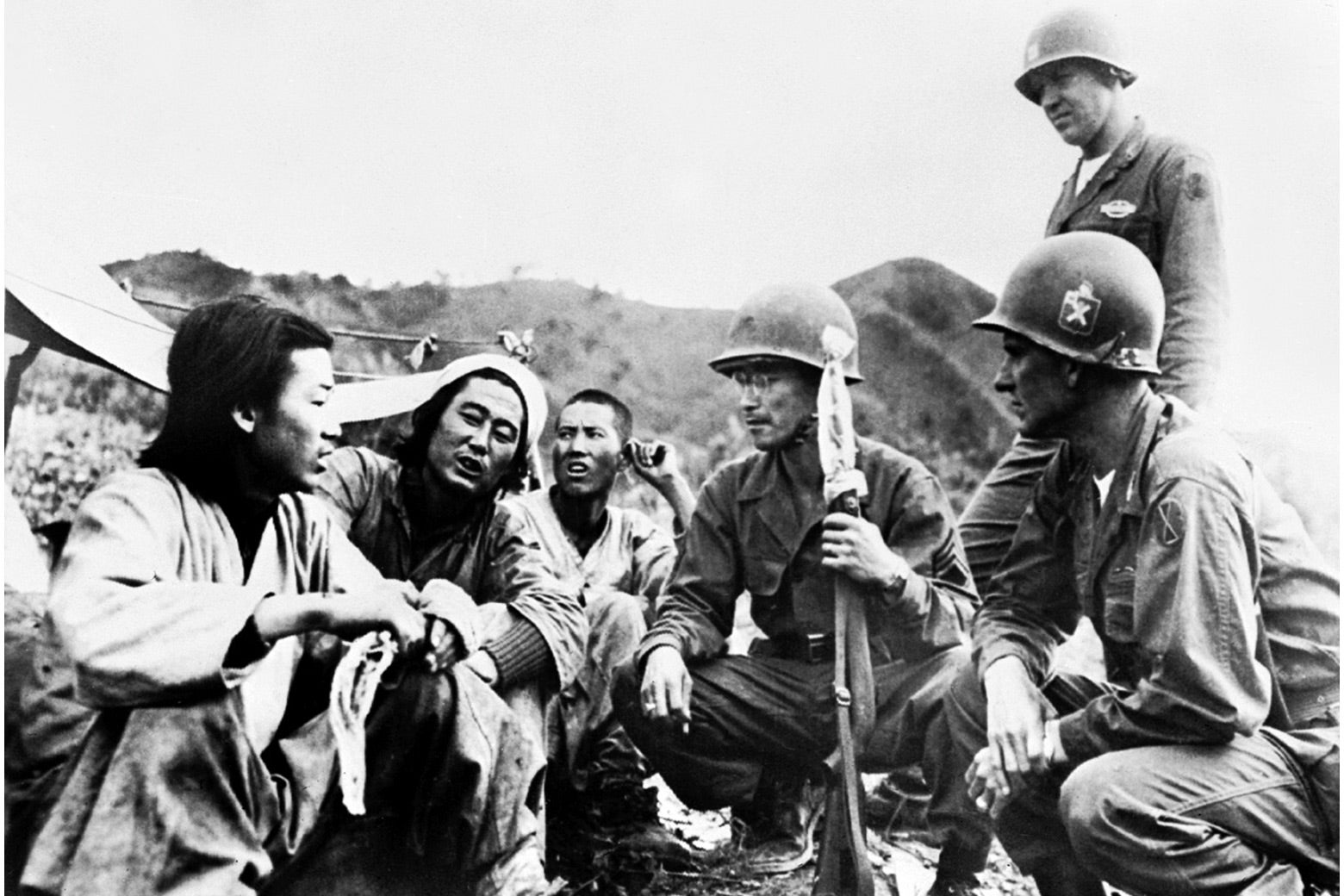 American soldiers crouch down to talk with North Koreans in a historical black-and-white photo.
