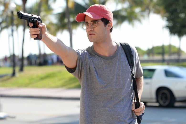 Darren Criss wears a red hat and round glasses and holds up a gun.