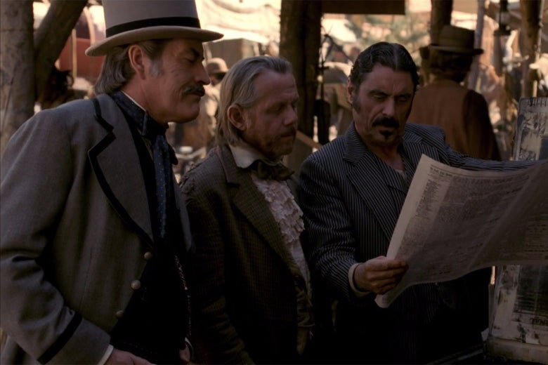 Cy Tolliver (Powers Boothe), E.B. Farnum (William Sanderson), and Al Swearengen (Ian McShane) read a copy of the Black Hills Weekly Pioneer in a still from Deadwood.