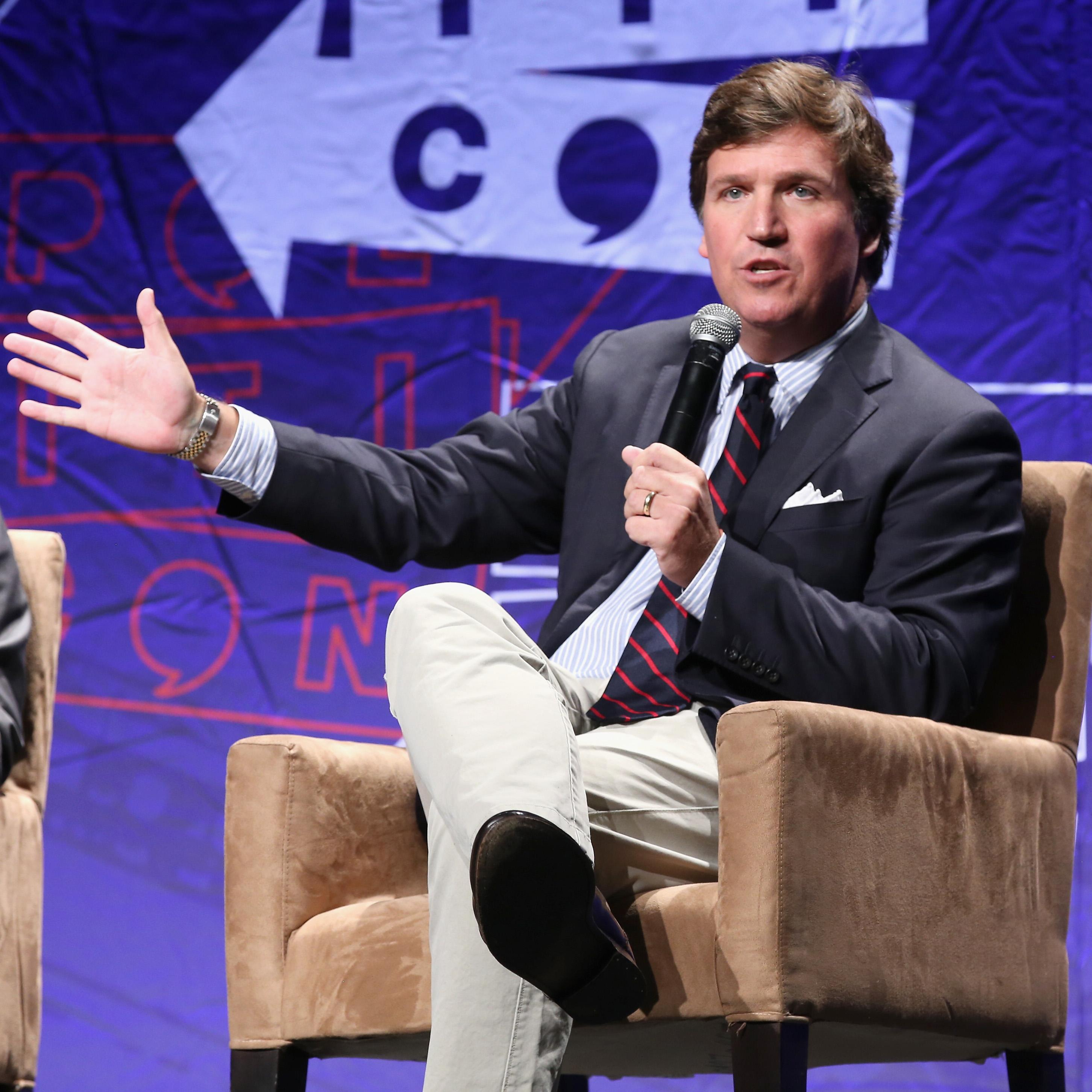 Tucker Carlson speaks into a microphone as he sits on a stage.