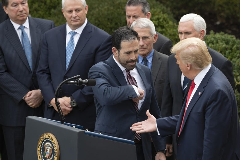 President Trump holds out his hand to an executive during a Rose Garden press conference on the coronavirus pandemic.