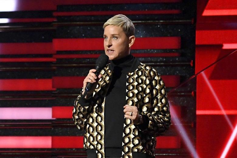 Ellen speaks onstage, holding a mic