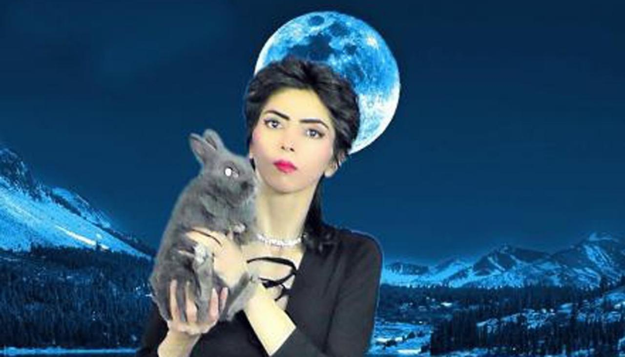 An image of YouTube shooter Nasim Aghdam holding a rabbit in front of a moon and mountains.