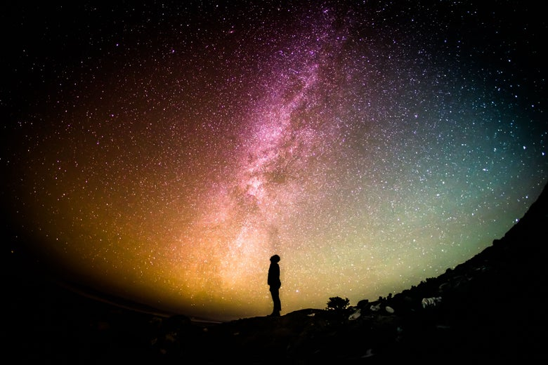 A person stands gazing up at a multicolored swirl of stars.