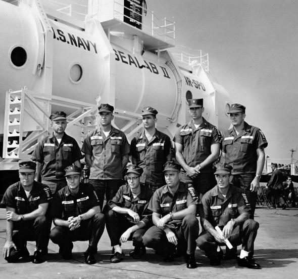 Sealab II's first crew poses in front of the U.S. Navy's new habitat before it's lowered to the seabed.