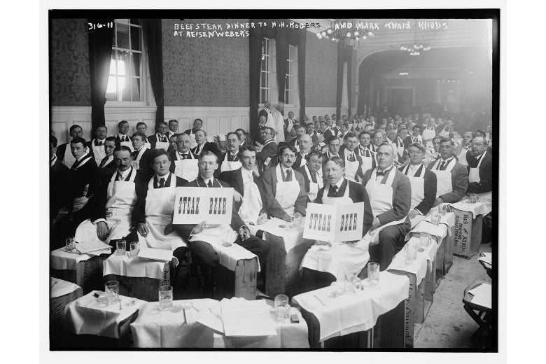 A black-and-white photo of a crowd of men in a restaurant in aprons with signs that say STEAK and BEER.