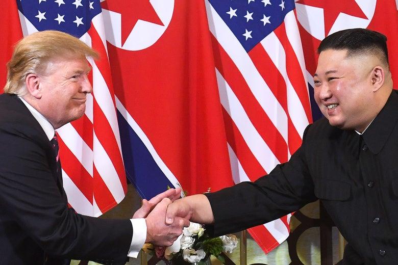 Donald Trump and Kim Jong-un, seated, shake hands.