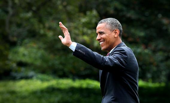 U.S. President Barack Obama waves as he walks toward Marine One while departing the White House.