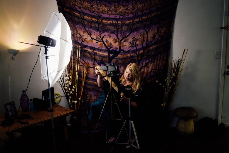 A woman holds a rainstick with a camera and lighting gear pointed toward her.