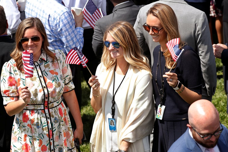Three young women in professional dress, two of whom are wearing ID badges, wave miniature flags.