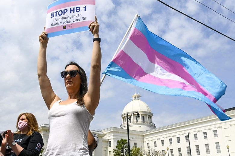 A woman holds up a Stop HB 1 sign while another person waves a transgender pride flag outside the Alabama State House
