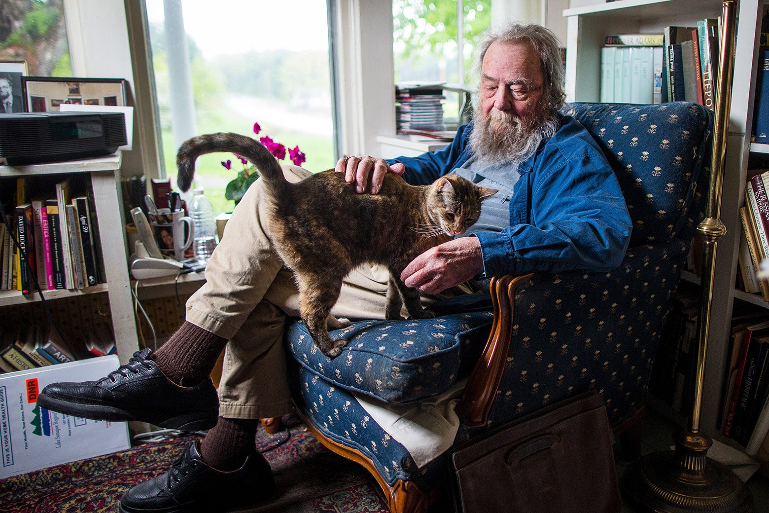 Donald Hall in a chair with a cat on his lap.