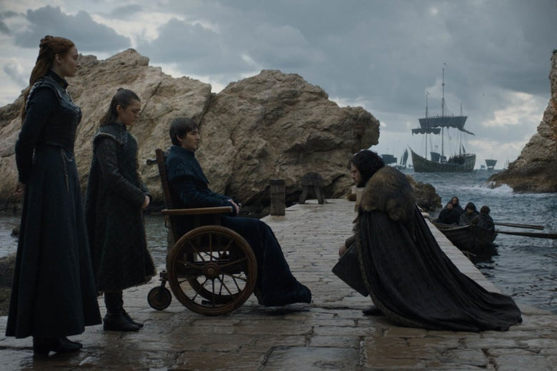 Sansa, Arya, and Bran Stark stand on a jetty with a ship in the background. Jon Snow kneels before them.