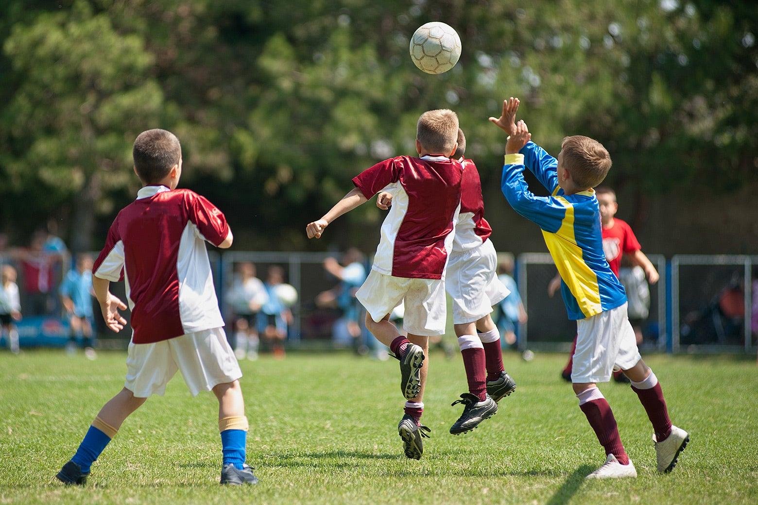Boys playing organized soccer on a field.