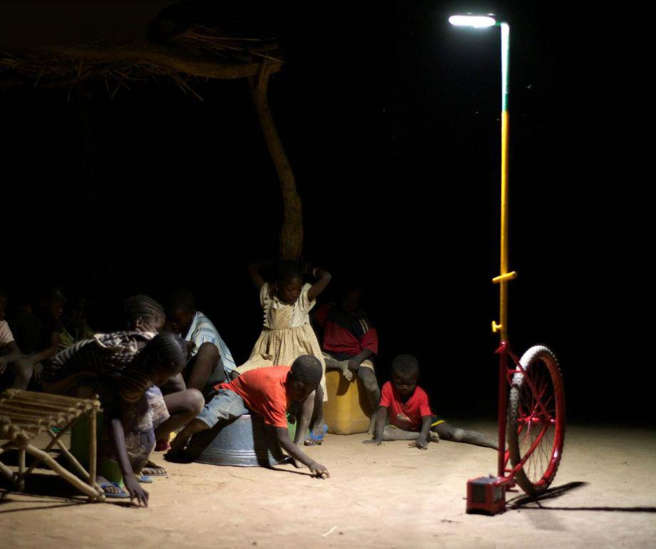 Children gather under an LED light in Mali.
