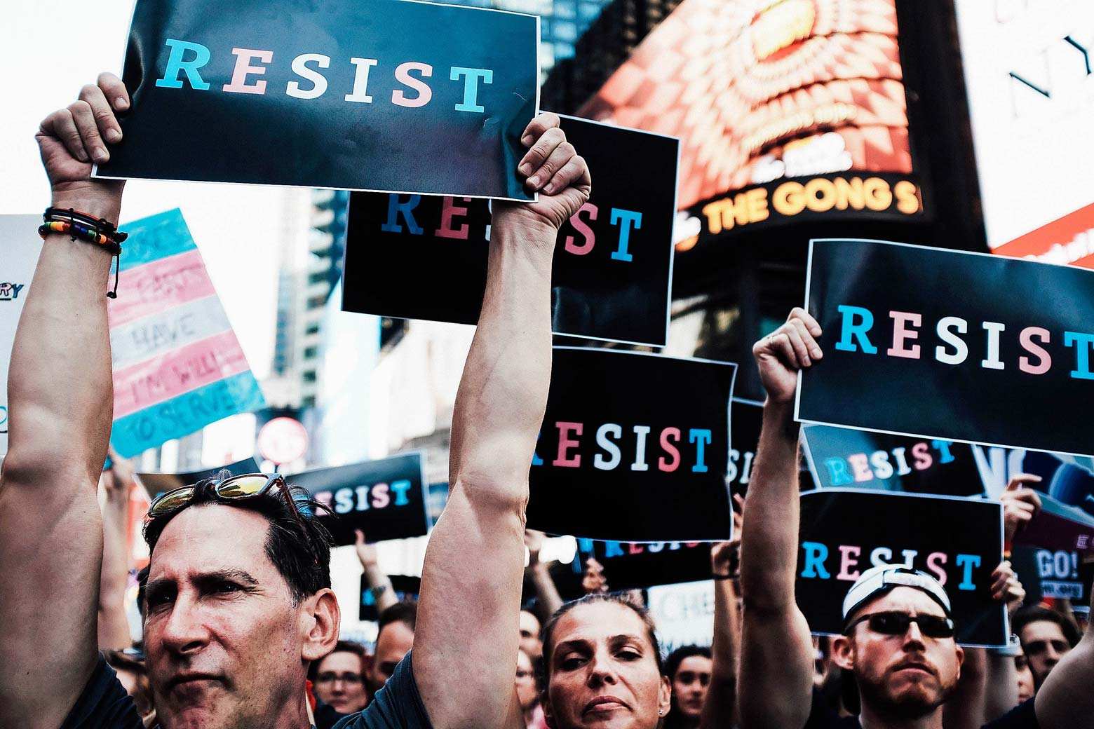 """Protesters hold up signs that say, """"RESIST"""" with letters in the blue, white, and pink colors of the transgender symbol."""