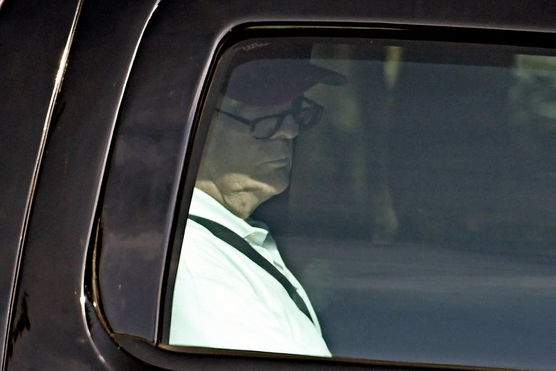A photograph taken through Donald Trump's limo window shows him wearing glasses as he reads something out of frame.