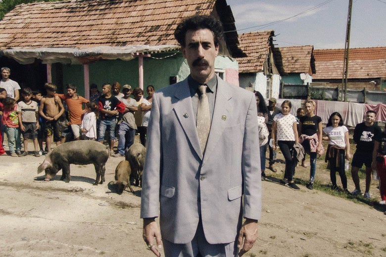 The actor looks very nice in his signature gray suit and Groucho Marx mustache, standing in front of a group of kids in a village