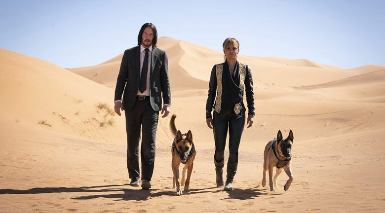 Keanu Reeves, Halle Berry and two dogs walking in a desert.