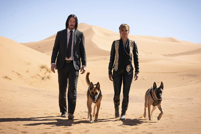 Keanu Reeves, Halle Berry, and two dogs striding across a desert.