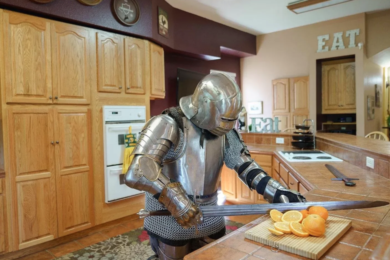 A knight slicing oranges in a large kitchen.