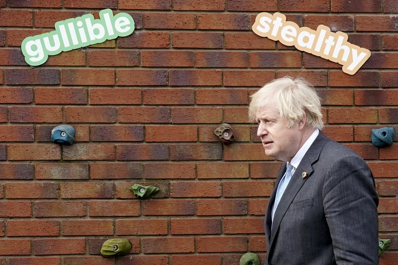 """Boris Johnson stands in front of a wall at a school, with two signs reading """"Gullible"""" and """"Stealthy"""" above his head."""